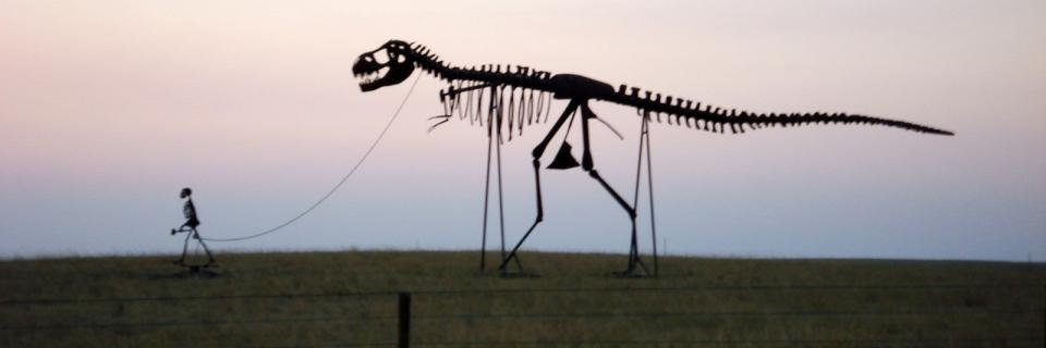 Statue of human skeleton with a T. Rex skeleton on a leash.